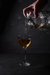 Pouring an alcoholic cocktail drink from a mixing glass filled with ice cubes, through a julep strainer into a nick and nora glass, dark backdrop
