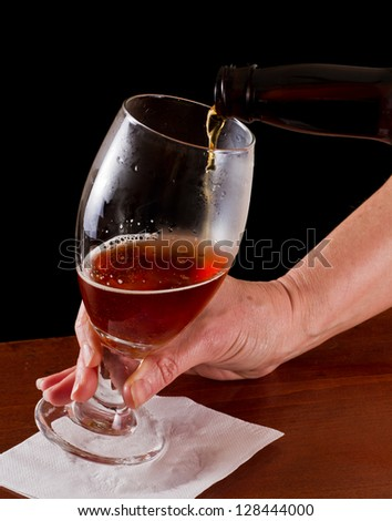 pouring an irish red ale beer into a chalice on a black background