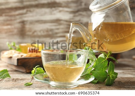 Pouring aromatic lemon balm tea into cup on wooden table