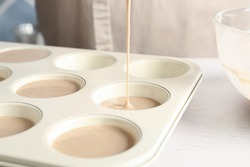 Pouring batter into cupcake tray at white table in kitchen, closeup