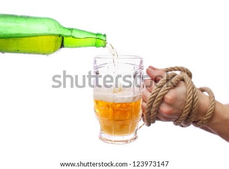 Pouring beer into a mug, motion shot. Bound hands hold a glass.