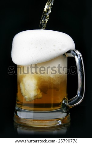 Pouring beer into mug over black background