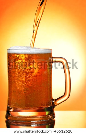 Pouring beer into mug over orange background