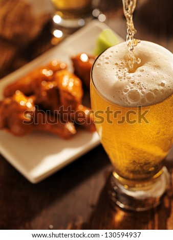 pouring beer with chicken wings in background