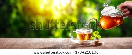 Pouring black tea into glass cup on wooden table