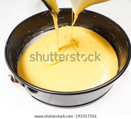 Pouring cake mixture into a black cake tin.