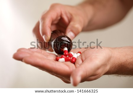 Pouring capsules from a pill bottle into hand