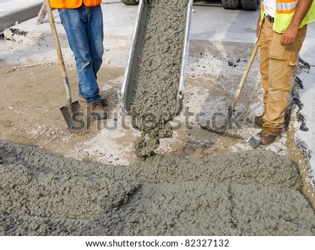 Pouring cement on newly paved road