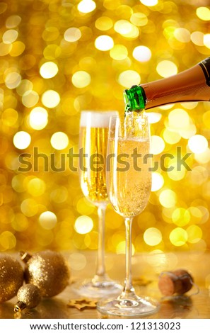 Pouring Champagne in a flute with a festive background. very shallow depth of field, focus on near glass. #121313023