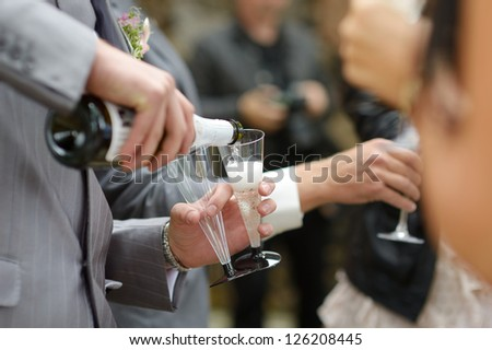 Pouring champagne into a glass on a wedding celebration