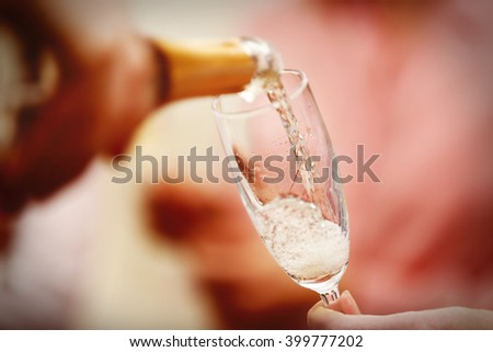 Pouring champagne into glass at hen-party, close up #399777202