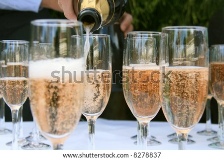 Pouring Champagne into wine glasses