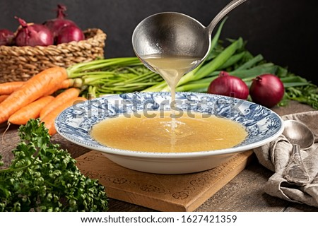 Pouring chicken bone broth from a ladle into a vintage plate, with fresh vegetables in the background Сток-фото ©