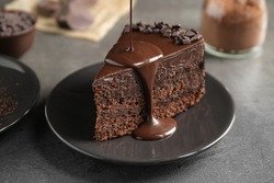 Pouring chocolate sauce onto delicious fresh cake on grey table, closeup
