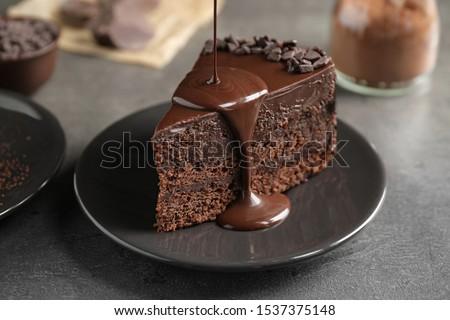 Pouring chocolate sauce onto delicious fresh cake on grey table, closeup Foto stock ©