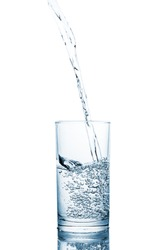 Pouring clean drinking water on a transparent glass. For health concepts. Isolated white background