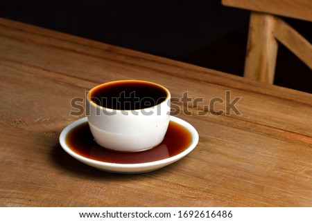 Pouring coffee into overflowed white porcelain mug with saucer. Cup with overflowing coffee. Full cup of coffee on wooden table with coffee spilled in saucer under the mug. ストックフォト ©