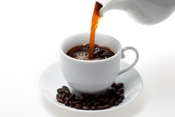 Pouring coffee into white coffee cup and beans on white background