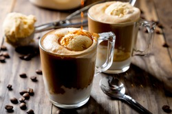 Pouring coffee on vanilla ice cream to make an affogato coffee on a rustic wooden table