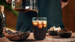 Pouring cold brew iced coffee in glass cup with ice cubes