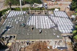 Pouring concrete,  commercial concreting floors of buildings in construction. Boom pump pouring concrete machine, workers working in concrete casting. Air top view