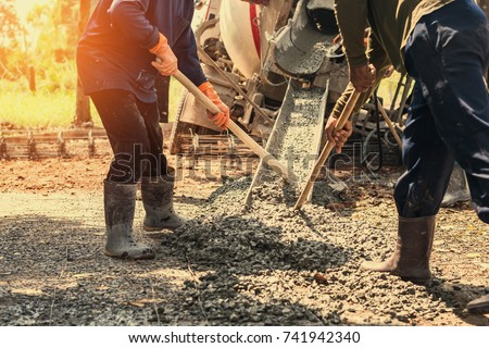 pouring concrete with worker mix cement at construction site