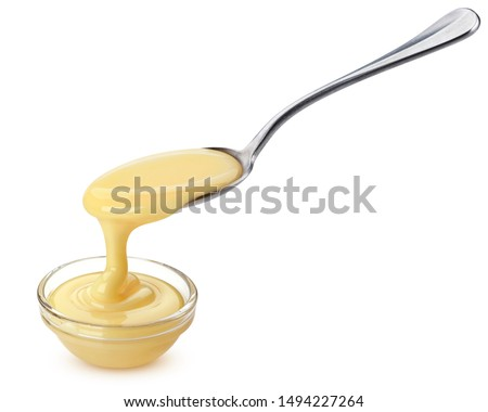 Pouring condensed milk with spoon isolated on white background with clipping path, delicious flowing creamy evaporated cream #1494227264