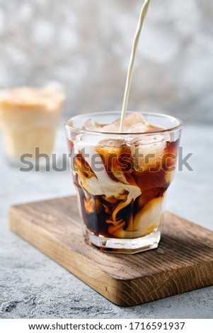 Pouring cream in iced coffee in rocks glass