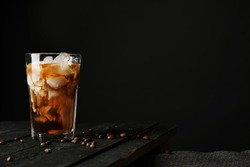 Pouring cream into a glass with iced coffee on table and black background
