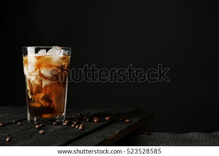 Pouring cream into a glass with iced coffee on table and black background #523528585