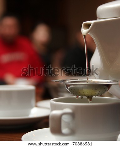pouring darjeeling tea from a white tea pot into a cup and saucer through a silver tea strainer