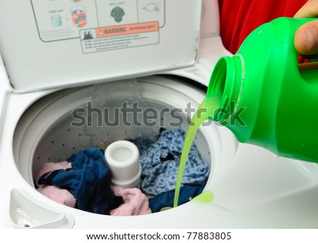 Pouring Detergent into the wash machine.