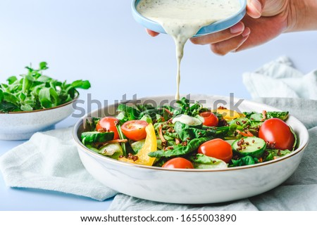 Pouring Dressing on Garden Salad on a light green cloth and light blur background Foto stock ©