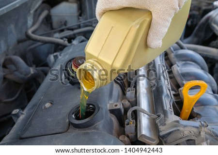 pouring engine oil into the engine #1404942443