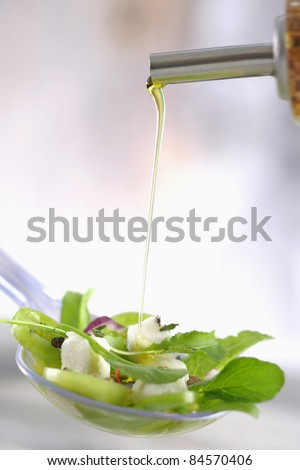 Pouring french dressing onto a mixed salad with diced goat's cheese