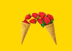 Pouring fresh ripe strawberries from waffle cones on bright yellow pink background. Organic vegan sweets healthy diet summer berries concept