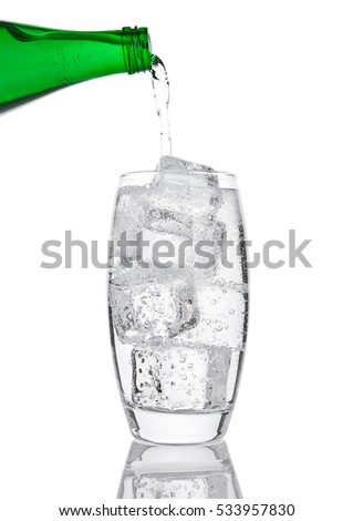 Pouring fresh sparkling water from bottle to glass on white background #533957830