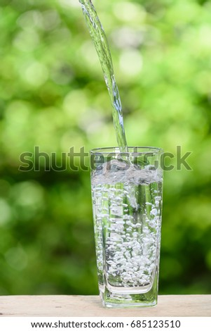 Pouring fresh water into glass on wood table with green nature background