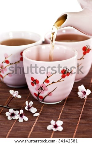 Pouring green tea into cups with cherry blossom design