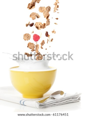 Pouring healthy cereal into a bowl with milk splash