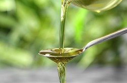 Pouring hemp oil into spoon on blurred background, closeup