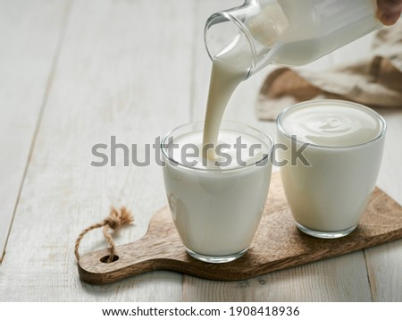 Pouring homemade kefir, buttermilk or yogurt with probiotics. Yogurt flowing from glass bottle on white wooden background. Probiotic cold fermented dairy drink. Trendy food and drink. Copy space left