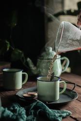 pouring hot coffee in green enamel mug