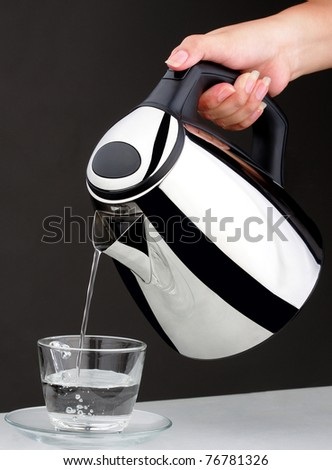 Pouring hot water from electric kettle a useful kitchenware