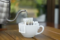 Pouring hot water into cup with drip coffee bag from kettle on wooden table, closeup