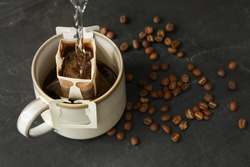 Pouring hot water into cup with drip coffee bag on black table, closeup