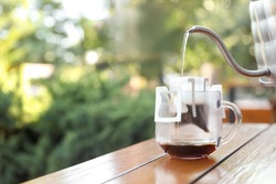 Pouring hot water into glass cup with drip coffee bag from kettle on wooden table. Space for text