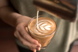 Pouring latte art into the flat white glass