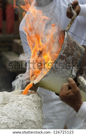pouring liquid metal into mold - stock photo