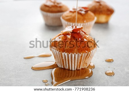 Pouring maple syrup onto tasty bacon muffin on table